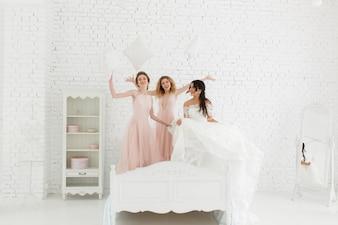 Mädchen sind verrückt vor der Hochzeit, springen auf dem Bett und kämpfen Kissen.