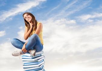 Mädchen sitzt auf einem Bücher