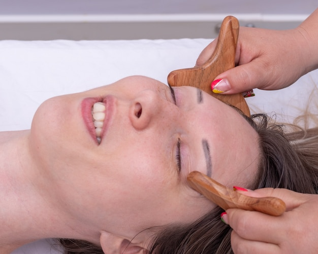Madero-therapie, anti-aging-entspannungsmassage - die hände des masseurs massieren die stirn des mädchens mit einem natürlichen holzmassagegerät. facelifting massage, korrektur und entfernung von mimikfalten