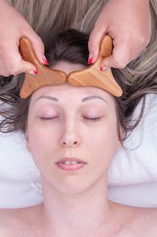 Madero-therapie, gesichts- und nackenmassage, anti-aging-entspannungsmassage - hände des masseurs massieren die stirn des mädchens mit einem natürlichen holzmassagegerät, nahaufnahme. gesichtslifting-massage