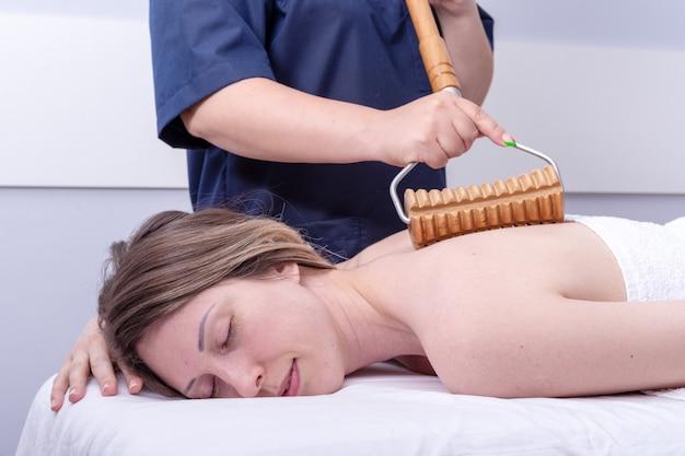 Madero-therapie, lymphdrainage-massage - frau mit spa-rückenmassage im schönheitssalon mit holzrollenmassagegerät. körperpflegekonzept