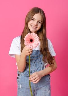 Mädchen 10 jahre alt in einem jeanshemd mit einer rosa gerberablume in ihren händen auf einem rosa teenager