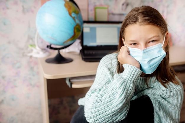 Mädchen 10 jahre alt in einer maske auf fernunterricht zu hause. das kind ist gelangweilt, es ist müde