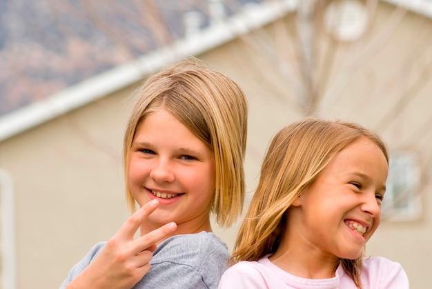 Mädchen (8-11) gestikulierend mit haus im hintergrund, lächelnd, porträt