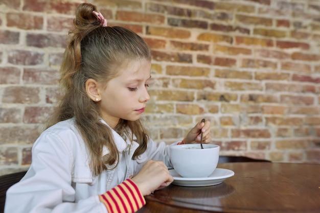 Mädchen, 9, 10 jahre alt, mit einer tasse heißer schokolade, die im café am tisch sitzt, kopierraum