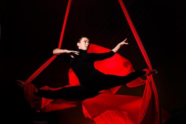 Mädchen aerialist macht bindfäden auf luftleinwänden. akrobatik in der luft
