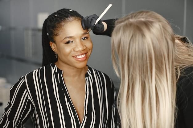 Mädchen afrika. frau, die augenbrauen macht. mädchen in einem schönheitssalon.