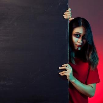 Mädchen als zombie gekleidet blick von hinter einer wand