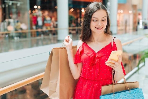 Mädchen am einkaufszentrum ihr telefon überprüfend