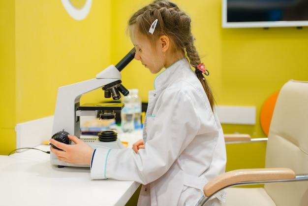 Mädchen am mikroskop, doktor spielend