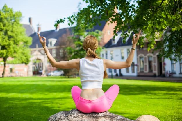 Mädchen am morgen, der yoga in der stadt tut