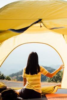 Mädchen am morgen im zelt und blick auf die berge in thailand aufwachen