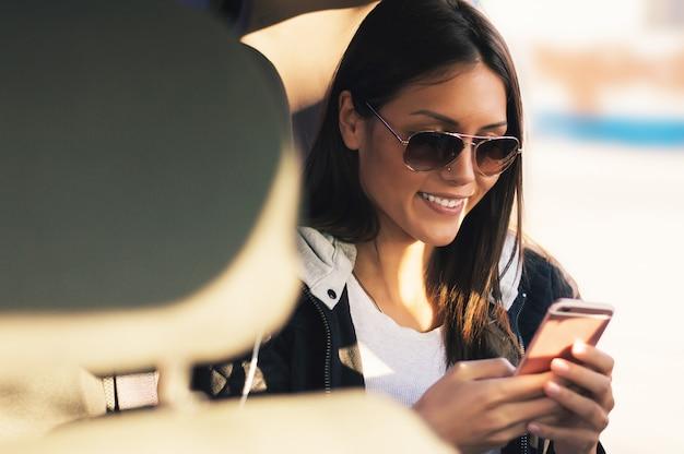 Mädchen am rücksitz telefon und mitteilung überprüfend