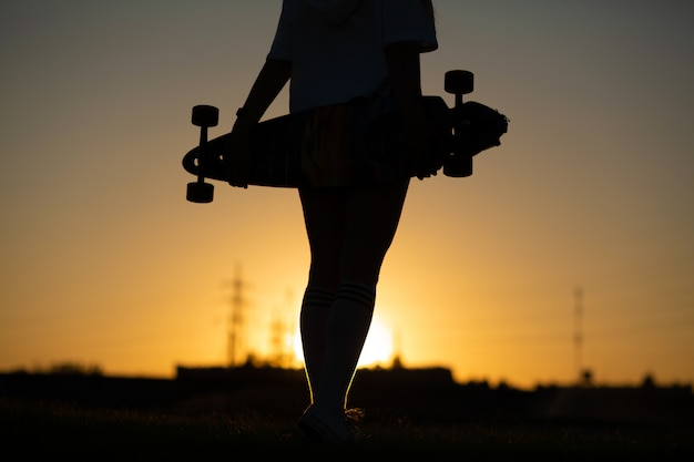 Mädchen am sonnenuntergang, der ein longboard in ihrer hand anhält