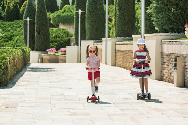 Mädchen am sonnigen tag. kinder im vorschulalter fahren roller im freien. glückliche süße kleine kinder, die auf der straße spielen