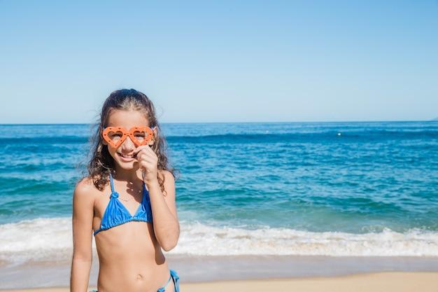 Mädchen am strand glücklich mit ihrer schutzbrille