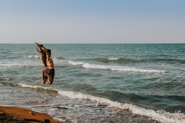 Mädchen am strand in die luft springen. sommer-konzept.