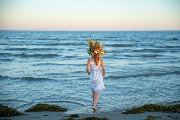 Mädchen am strand in einem weißen sommerkleid und mit einem kranz aus wildblumen betritt meerwasser