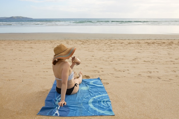 Mädchen am strand sitzt auf einem handtuch, das natürlichen nährstoffsaft trinkt.