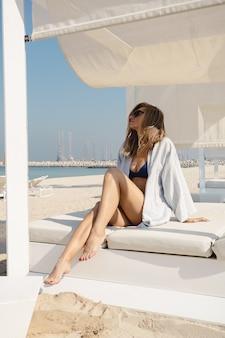 Mädchen am strand sitzt auf einer sonnenliege und genießt urlaub an einem sonnigen tag.