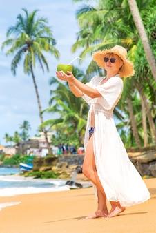 Mädchen am strand trinkt kokosnuss. selektiver fokus. natur.