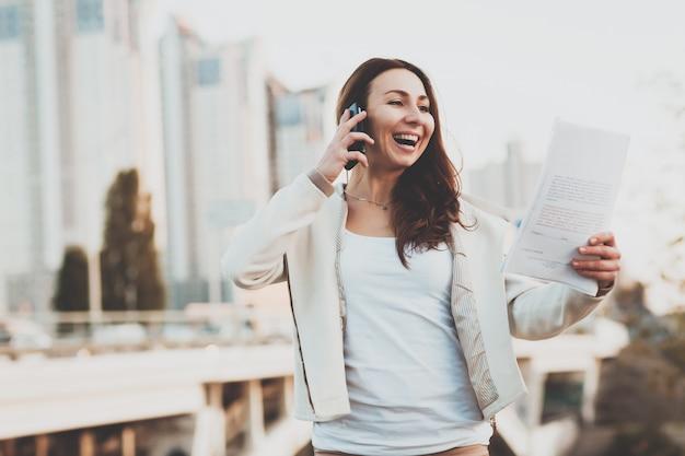 Mädchen am telefon, papiere mit gebäuden auf hintergrund