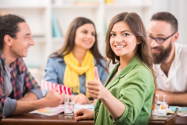 Mädchen am tisch zeigt sich daumen.
