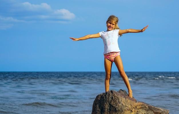 Mädchen am ufer des sees steht in einer schönen pose auf den felsen.