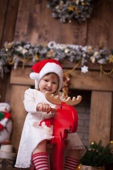 Mädchen am weihnachtsbaum mit geschenken reiten auf einem spielzeug los