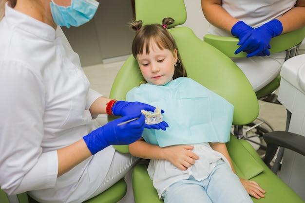Mädchen am zahnarzt, der gebisse betrachtet