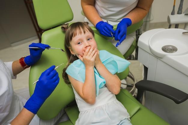 Mädchen am zahnarzt, der von der ausrüstung erschrocken wird