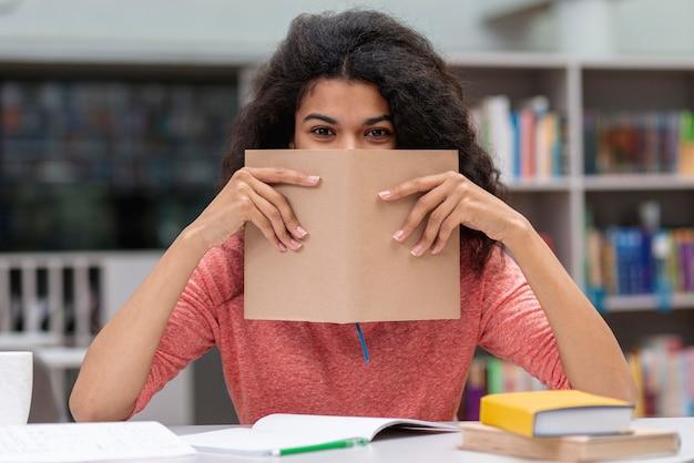 Mädchen an der bibliothek, die gesicht mit buch bedeckt