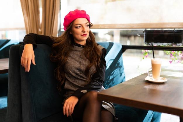 Mädchen an einem tisch in einem café mit einer tasse latte-kaffee. für jeden zweck.