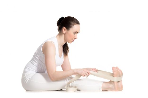 Mädchen arbeiten in yoga-klasse mit einem gurt
