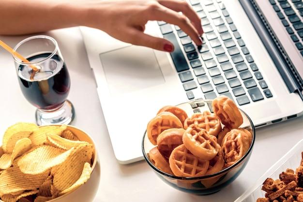 Mädchen arbeitet an einem computer und isst schnellimbiß