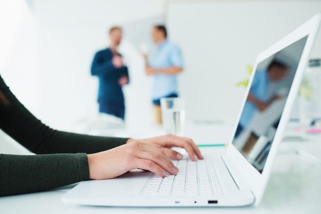 Mädchen arbeitet an einem laptop im büro. konzept der gemeinsamen nutzung und zusammenschaltung des internets
