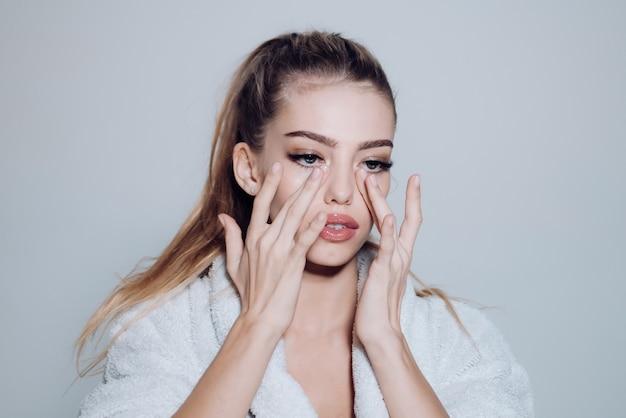 Mädchen auf beschäftigtem gesicht im bademantel, der gesicht mit cremegrauer oberfläche bedeckt frau mit gesunder haut dame kümmert sich um glatte haut hautpflege- und kosmetikkonzept