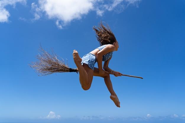 Mädchen auf dem besen, der vorgibt, hexe auf himmelshintergrund zu sein. foto in hoher qualität