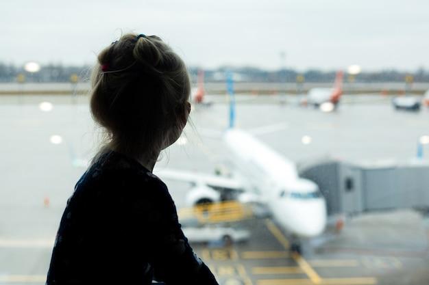 Mädchen auf dem flughafen vor dem fenster schaut auf das flugzeug und wartet auf den flug