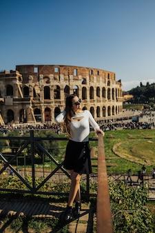 Mädchen auf dem hintergrund des majestätischen alten kolosseums in rom.