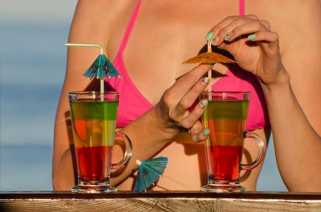Mädchen auf dem strandcocktail verziert mit dem meer im raum