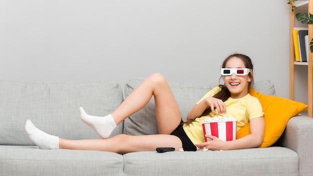 Mädchen auf der couch, die popcorn isst