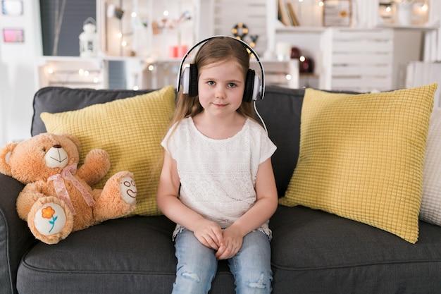Mädchen auf der couch mit kopfhörern