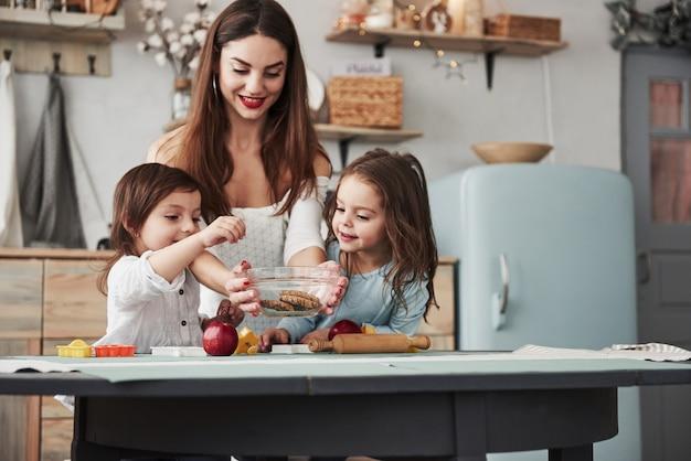 Mädchen auf der linken seite will jetzt diese süßigkeiten. junge schöne frau gibt die kekse, während sie mit spielzeug am tisch sitzen.