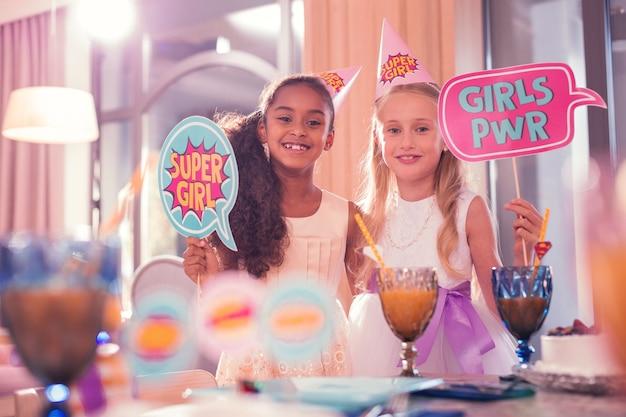 Mädchen auf der party. positive entspannte mädchen, die lächeln und zeichen über die macht der mädchen halten, während sie auf der party sind