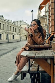 Mädchen auf der straße mit einem einweg-pappbecher. essen mitnehmen, durch die stadt spazieren.