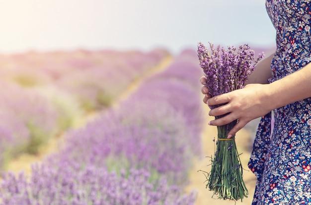 Mädchen auf einem blühenden gebiet des lavendels.