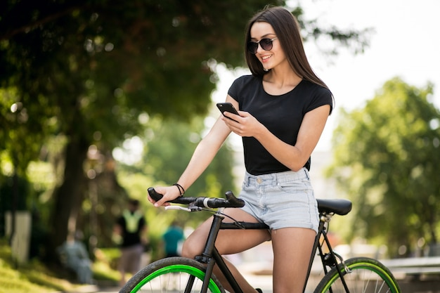 Mädchen auf einem fahrrad mit telefon