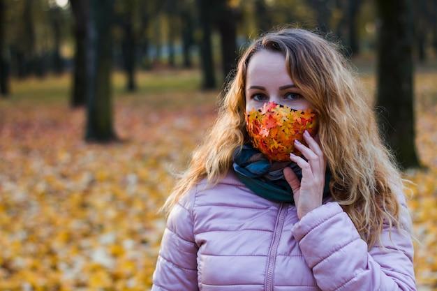 Mädchen auf einem hintergrund von bäumen in einem park in einer maske von einem virus mit herbstlaub