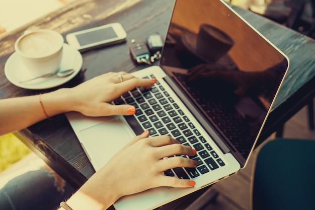 Mädchen auf einem laptop mit einer tasse kaffee eingeben es neben